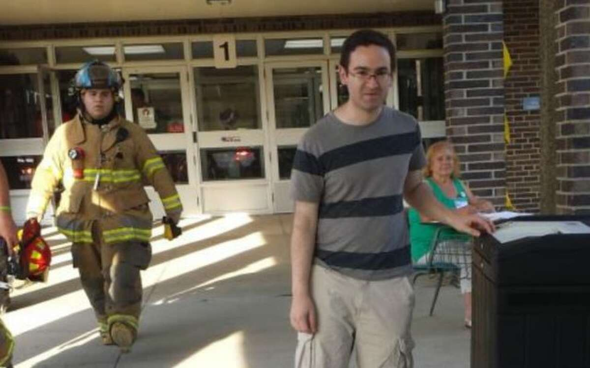 Mike Newman casts his ballot during the fire alarm at Hillcrest Middle School as firefighters exit the building.