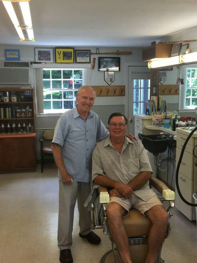 Nick Clericuzio, owner of Long Hill Hair Stylists, smiles with long-time customer Vincent Zujewski after completing a haircut on June 27. Zujewski, a member of Trumbull High School's Class of 1968, has been going to Clericuzio's barbershop since he was 16 years old. His most recent cut, which he will wear to his daughter's wedding in California this month, marked the 50-year anniversary since his first trim at Long Hill Hairstylists in 1966. — Steve Coulter photo