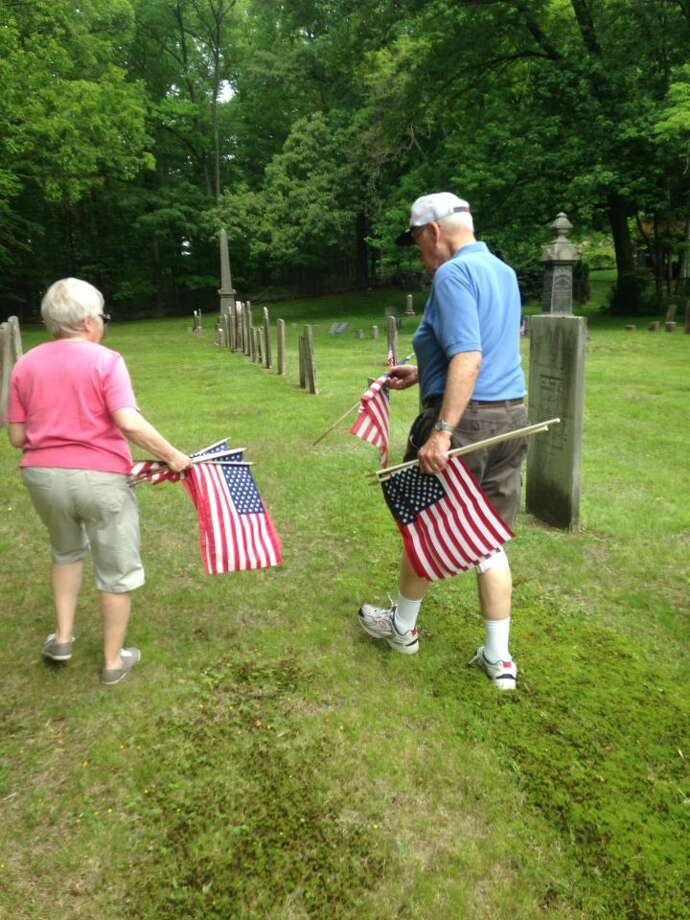 Trumbull residents Bill and Ruth Wakeley get ready to place flags at Riverside Cemetery.