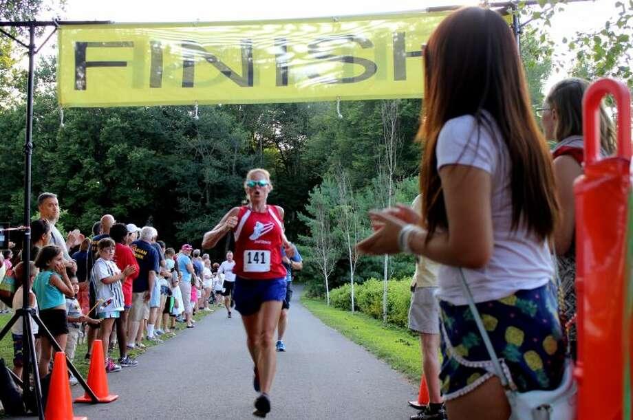 A Trumbull runner crosses the finishing line at last year's Sunset Run.