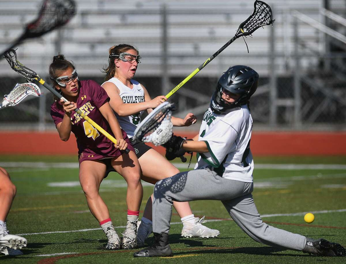 St. Joseph's Lily Ivanovich, left, fires a shot past Guilford goalie Sydney Widlitz during the Cadets 14-10 victory over top ranked Guilford in the girls lacrosse Class M semifinals in Monday at Cheshire High School.