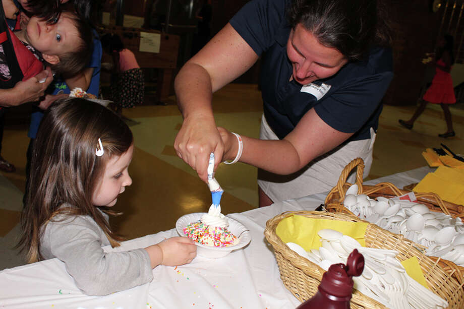 Annie Hughes, 3, accepts whip cream on her ice cream sundae from Trumbull High social studies teacher Katie Boland, adviser of the We the People team and ACE Foundation advisory board member. — Sue Berescik photo