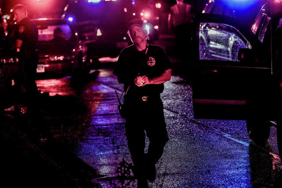 Alton Fire Department Battalion Chief Brad Sweetman walks back to his truck Saturday night after a pedestrian was struck by a vehicle on Broadway. It was the first of two serious accidents, one fatal, on Broadway this weekend.