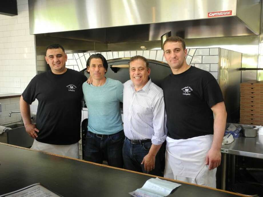 Aldo and Joe Criscuolo, middle, owners of Trumbull Pizza Company, stand in front of their brick oven that makes their family's famous super-thin crust pizza, as well as a bevy of other styles. The brothers opened the doors to their new business, located at 6528 Main Street, last week and have been delivering pies around town at a rapid pace ever since. — Steve Coulter photo
