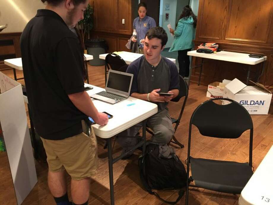 Trumbull High School senior Steven Baumann, seated, demonstrates his app TranslateU at the Mobile CSP App Expo in Hartford on May 24.