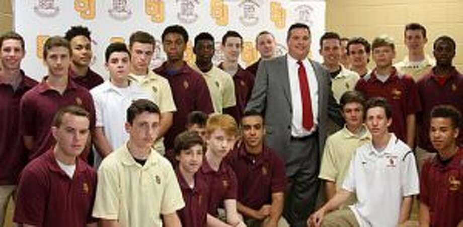 Paul Dudzinski is surrounded by members of the St. Joseph boys basketball team after Dudzinski was named coach of the Cadets.
