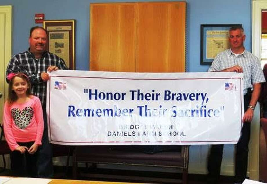 "Daniels Farm Elementary School student Bridget Walsh came up with the theme ""Honor their Bravery, Remember their Sacrifice"" for this year's Memorial Day Parade. She was congratulated by members of the Parade Committee last week."