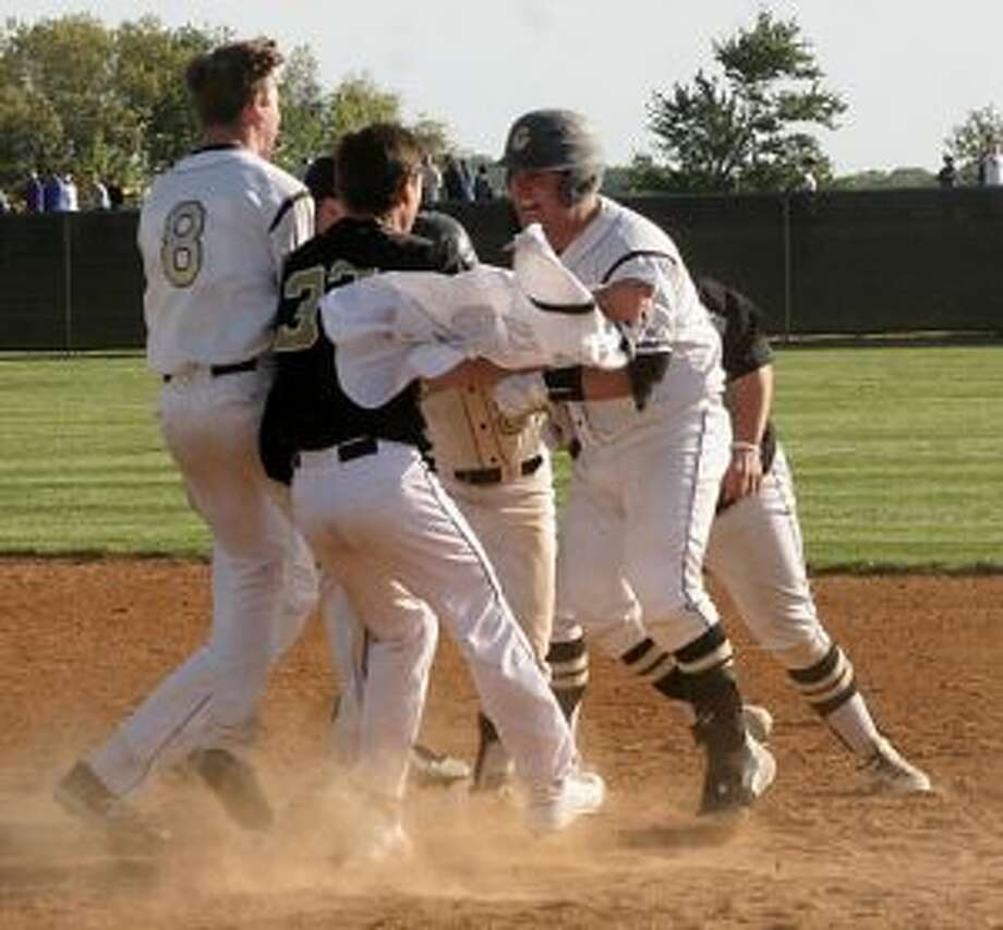 Trumbull High's Kris DiCocco draws a crowd after his RBI single plated the winning run. — Bill Bloxsom photos