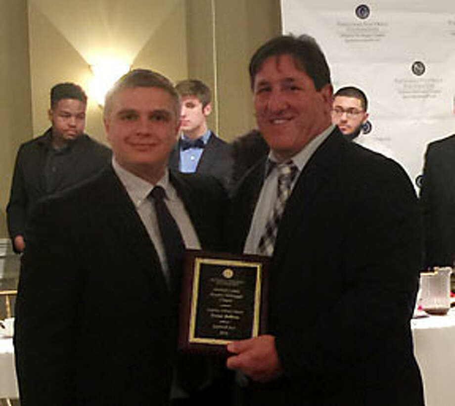 Trevor Bellows is presented with the National Football Foundation Scholar Athlete Award by John Barbarotta the Fairfield County Chapter president.