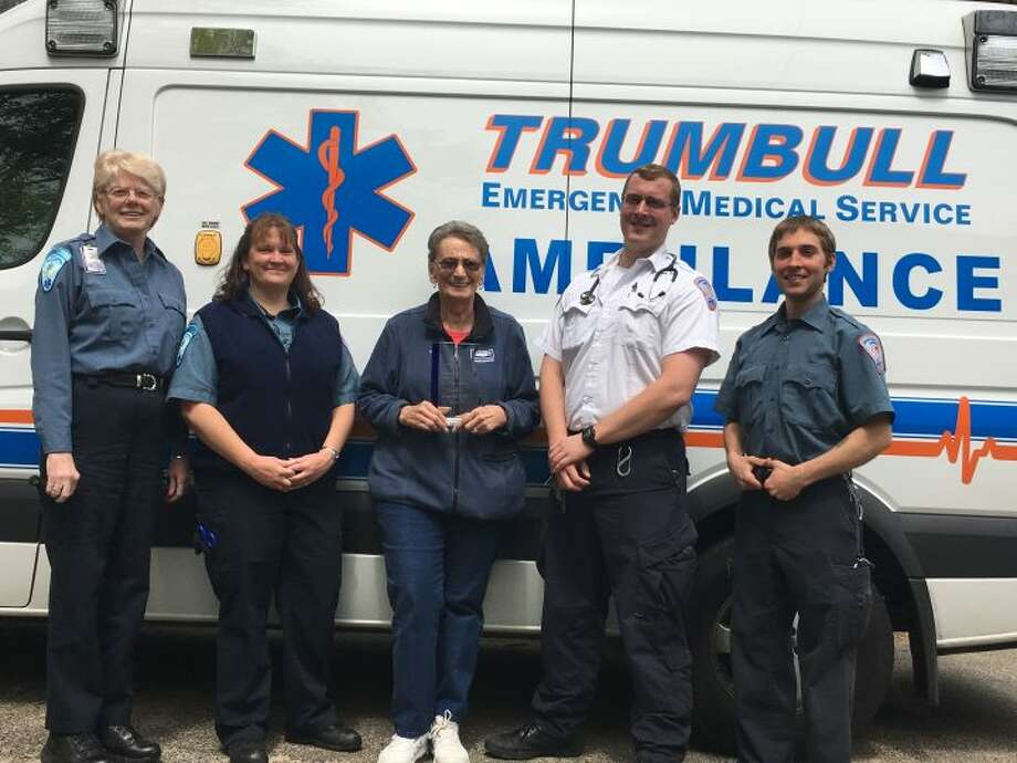 EMS executive administrative assistant Barbara Crandall, left, stands with staff members Jen DiJoseph, Chris Caulkins, and James Koch and EMT volunteer Di Watson, middle, outside the Trumbull Emergency Medical Services office on Middlebrooks Avenue. Watson, a 40-year member of Trumbull EMS and winner of the state's Volunteer of the Year award in 2015, holds the 2016 Governor's Award, which the department received at a reception in Hartford Monday, May 16. The Governor's Award, which Trumbull previously took home in 2014, is open to EMS departments across the state and is the top prize for emergency service organizations. — Steve Coulter photo