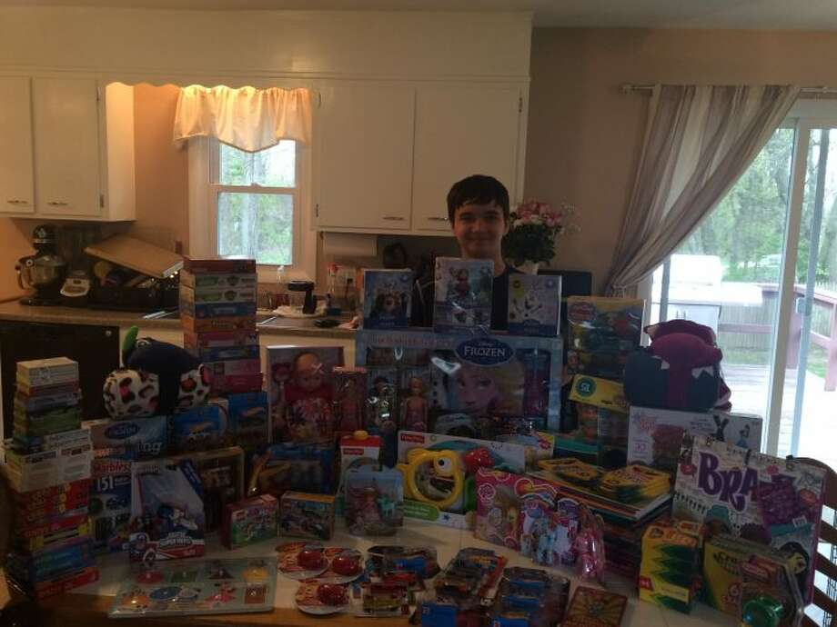 Madison Middle School student Ezekiel Cruz stands in his kitchen with all of the toys he collected.