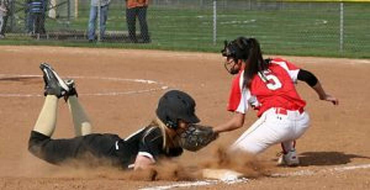 Trumbull High's Erica Fluskey slides safely into third base, as Greenwich's Julie Gambino makes the tag. - Bill Bloxsom photo