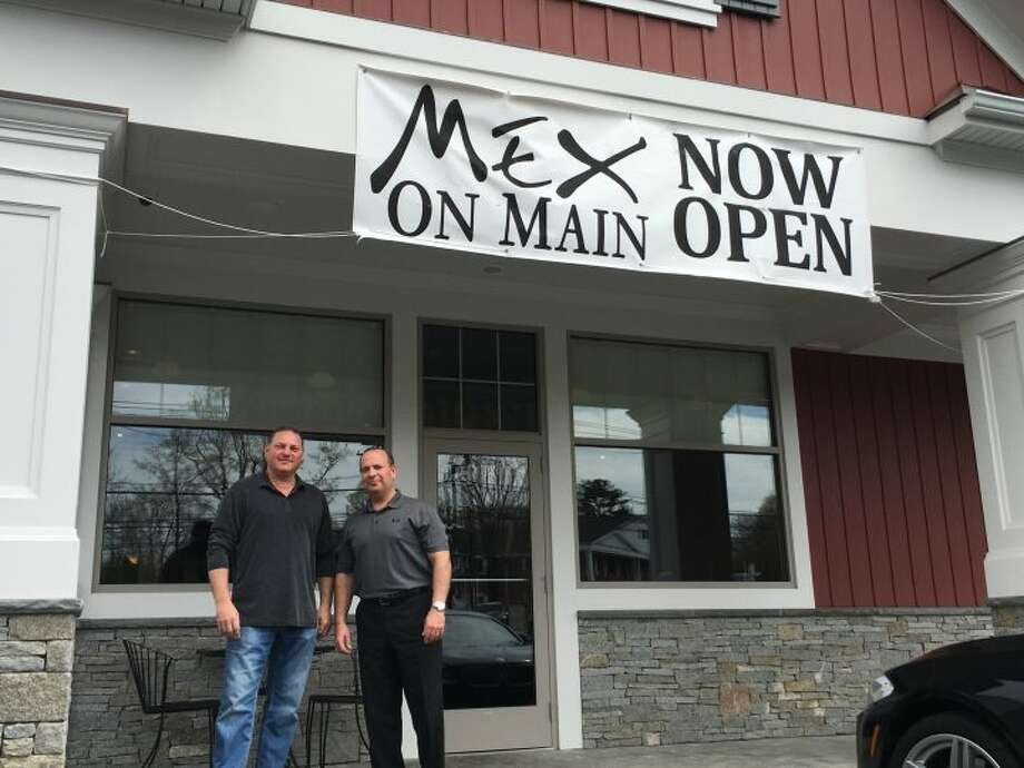 Nick Montanaro and Bill Neary, co-owners of Mex on Main, stand together under the new business's sign. The fresh Mexican grill restaurant opened in March and has been serving customers non-stop ever since. — Steve Coulter photo