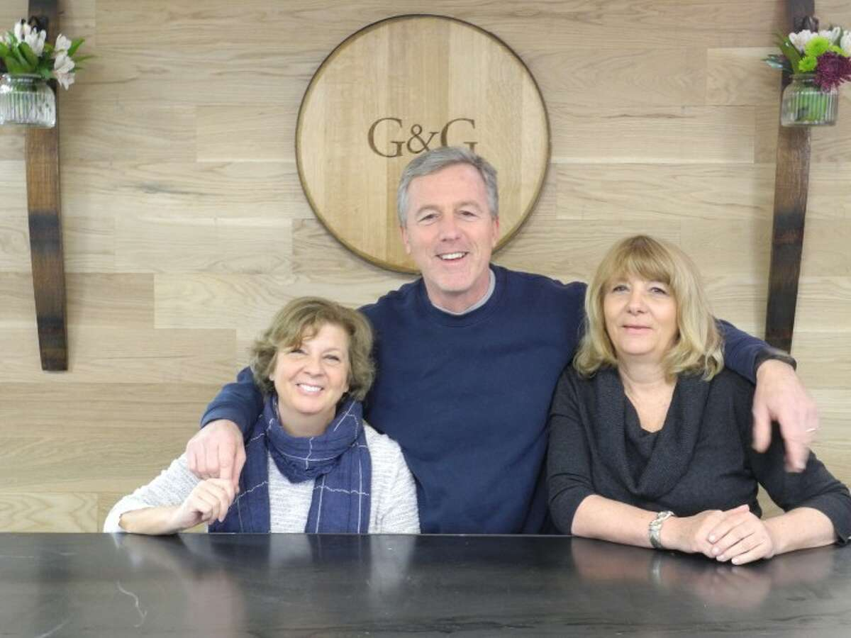 Ginna and Gene Donnelly, owners of G&G Liquors, stand behind the store's wine tasting table with manager Karen Ott. Trumbull's newest package store, located at 6528 Main Street, opened its doors on April 8 as part of the Village at Long Hill Green commercial development. - Steve Coulter photo