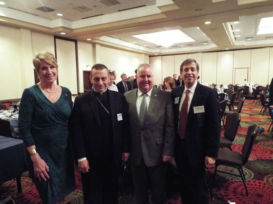 "State Rep. Laura Devlin, left, stands with Bishop Frank Caggiano and State. Rep Ben McGorty at the Kennedy Center's 65th anniversary dinner on April 7. Kennedy Center CEO Marty Schwartz, right, told The Times that the organization ""started by collecting money door to door in a cigar box has now developed into an organization serving 2,000 people a year from birth through seniors."" Caggiano served as the event's keynote speaker. — Joe Connolly photo"