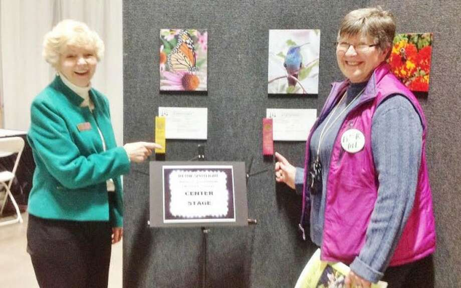 Long Hill Garden Club members Nancy Lenoce and Cheryl Basztura display some of their award-winning photos.