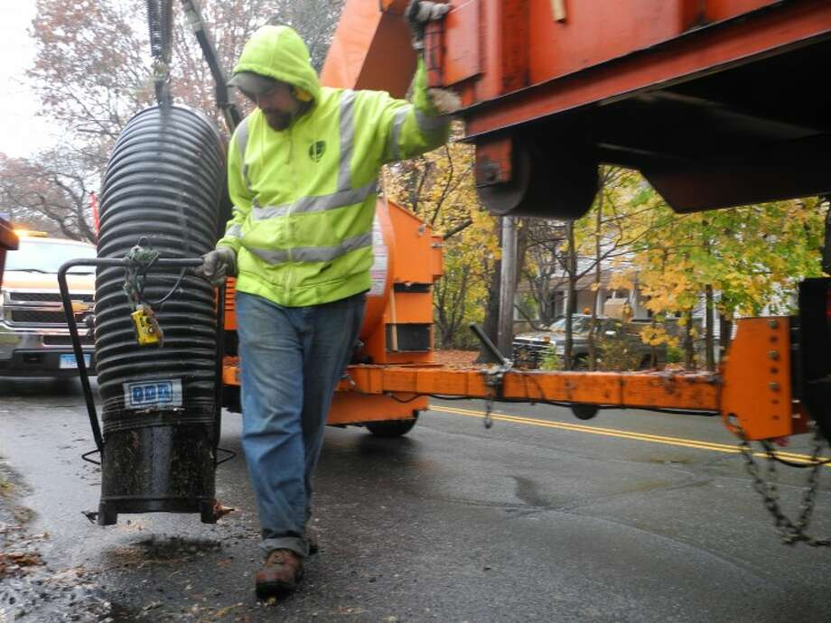 Public works employee Jim Carney operates a leaf vacuum machine during the highway department's leaf pickup program. — Steve Coulter photo