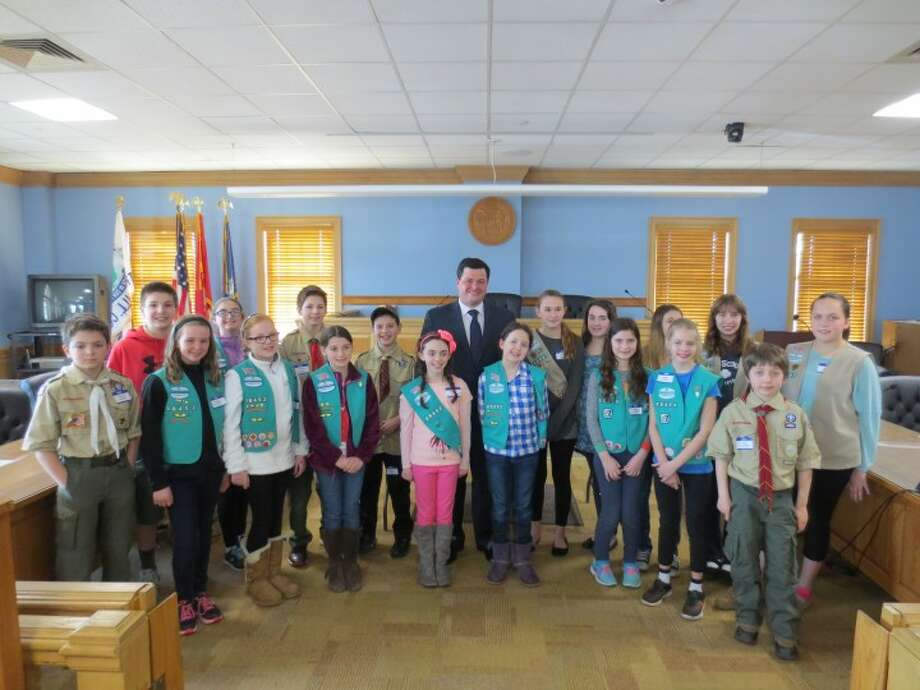 Eighteen Trumbull scouts pose for a photo with First Selectman Tim Herbst at the closing ceremony of Scouts in Government Day, which was held at Town Hall on March 16.