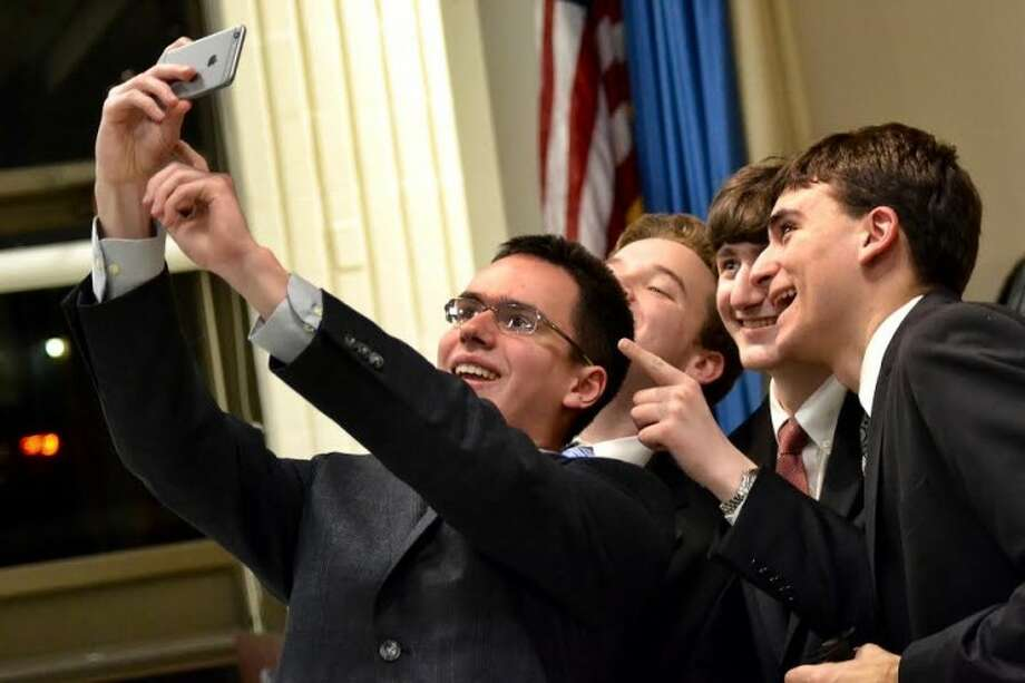 St. Joseph High School debate team member Ralph Rotondo holds up his iPhone to take a selfie with teammates Augustus LeRoux, Edward Szalan and Alexander Giannico after defeating the Trumbull High School at the Trumbull Library's fifth annual One Book, One Town kick-off debate. — Lisa Romanchick photo