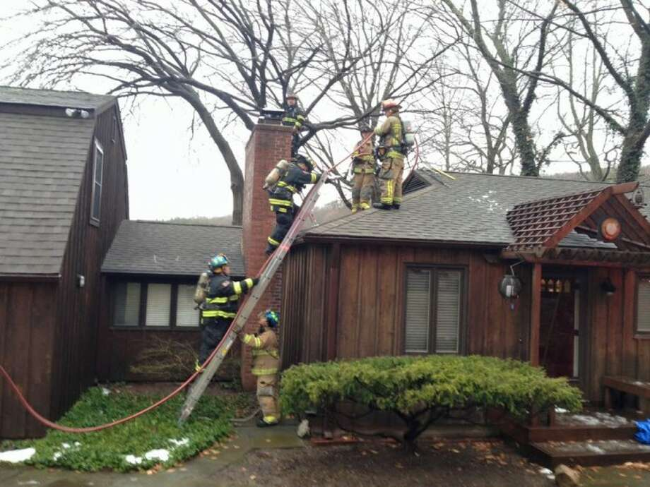 Nichols and Trumbull Center fire crews climb up a ladder to get a better look at a reported chimney fire on Hemlock Trail. — Trumbull Volunteer Fire Company, No. 1, Inc. photo