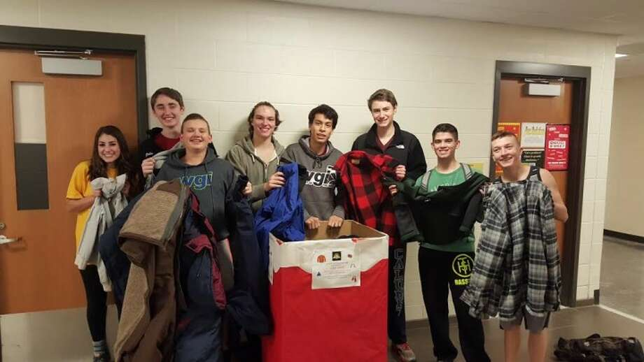 Members of the Trumbull High School Golden Eagle Marching Band display some of the coats they collected this year.