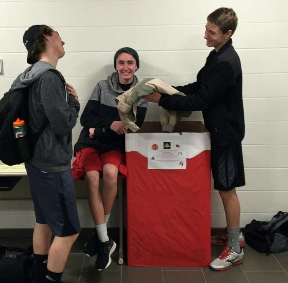 Jack Duda, John Targowski and Josh Merkin collect coats at the high school for the marching band's coat drive that is now running through the month of January.