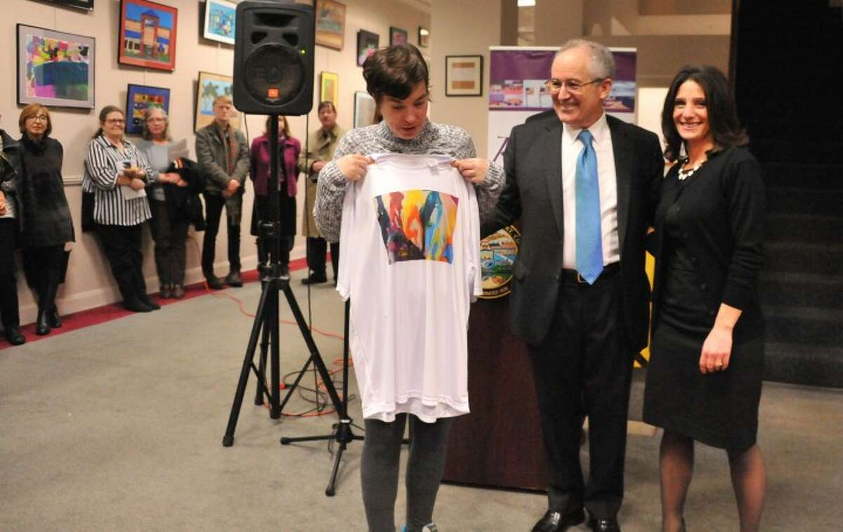"""Lisa Kellersman of Trumbull, left, created """"Colors"""" painting featured in The Kennedy Center's """"A Unique Perspective"""" Calendar for January. She is congratulated by Armando Goncalves, center, Southern Connecticut Market President, People's United Bank, and Karen Galbo, right, Director of People's United Community Foundation. More than 150 guests recently attended the debut of the Kennedy Center's Annual Calendar Reception at Gallery@999, located in the Margaret E. Morton Government Center in Bridgeport. The artwork will be on display for public viewing until the end of January. People's United Community Foundation was the underwriter of this beautiful, four-color calendar that raises needed funds for The Kennedy Center's Expressive Arts Program."""