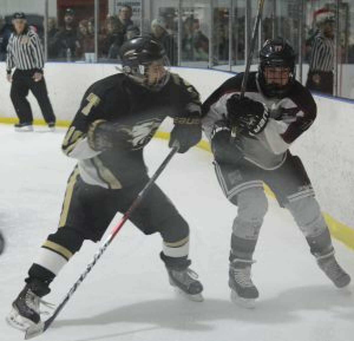 Trumbull's John Guerrera goes into the corner with Milford's Jason Lavallee.