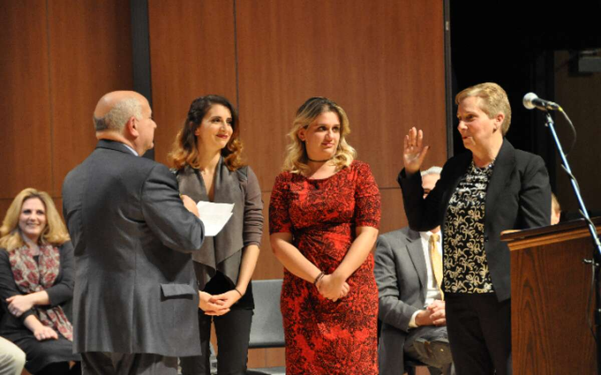 Tom Tesoro administers the oath of office to his wife, First Selectman Vicki Tesoro Monday at Trumbull High School. The two were joined on stage by daughters Melissa and Laura. - Bill Chin photo