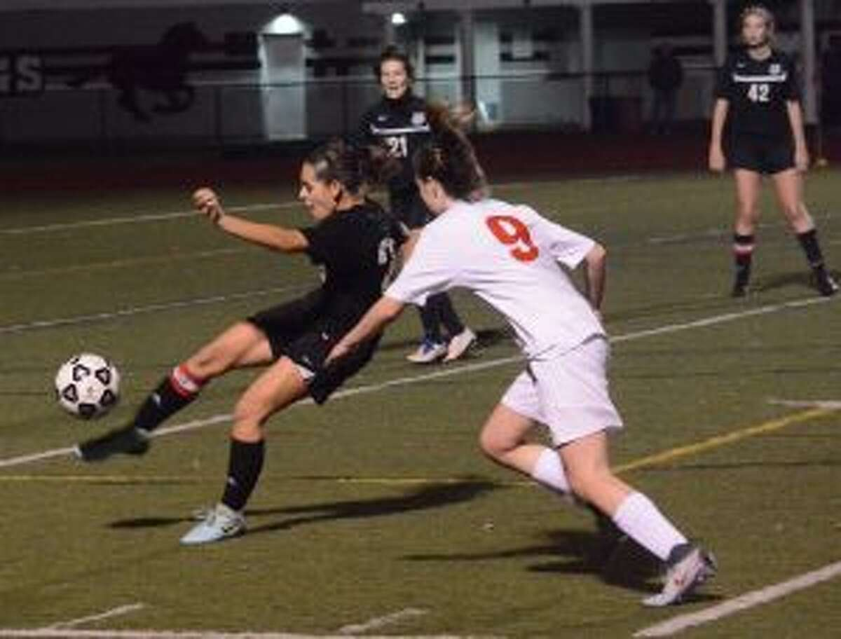 Eva Solano clears the ball, before Warde's Bridget King can challenge.