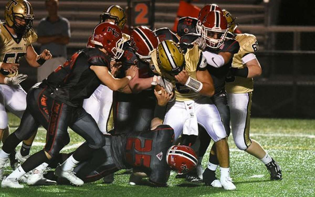 The New Canaan defense wraps up Trumbull QB Colton Nicholas during Friday night's football game at Dunning Field. - Dave Stewart photo
