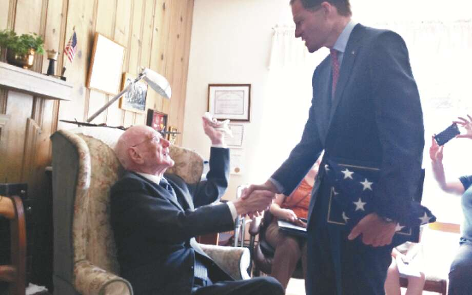 U.S. Sen. Richard Blumenthal presents WWII veteran George Bekech, 94, of Trumbull, with a folded American Flag as a token of thanks for his service and sacrifice. Bekech lost his hearing in the war. — Donald Eng