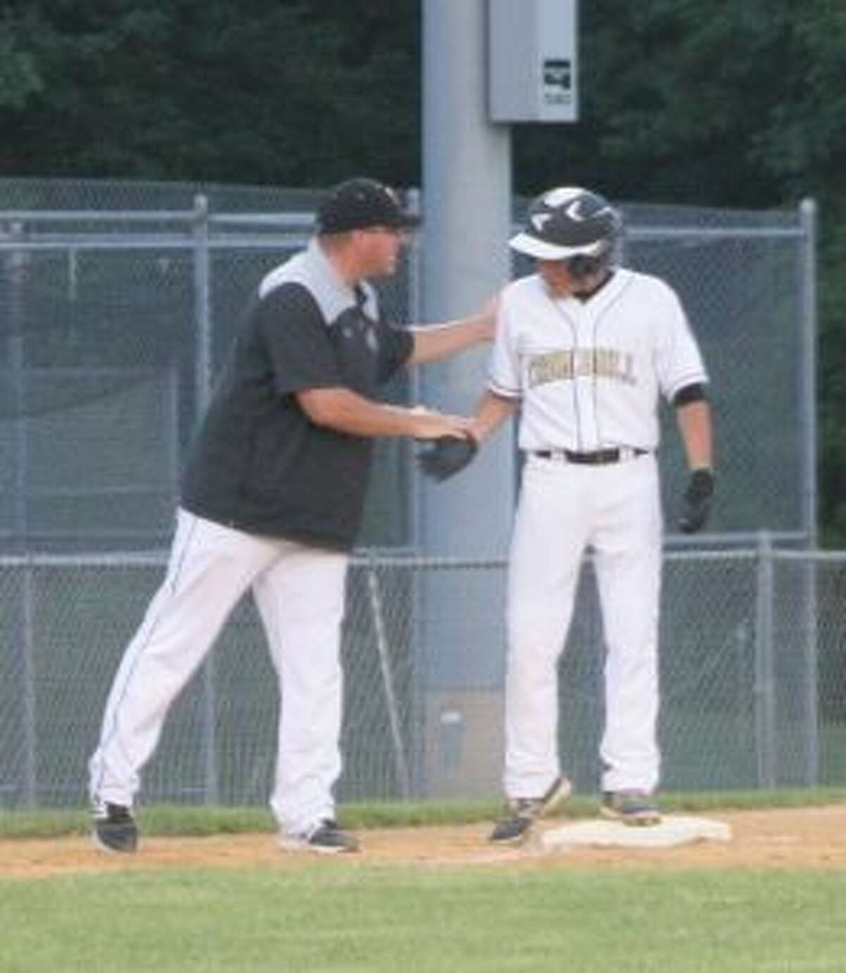 Trumbull head coach Mike Buswell greets Brandon Buda after his triple in the third inning.