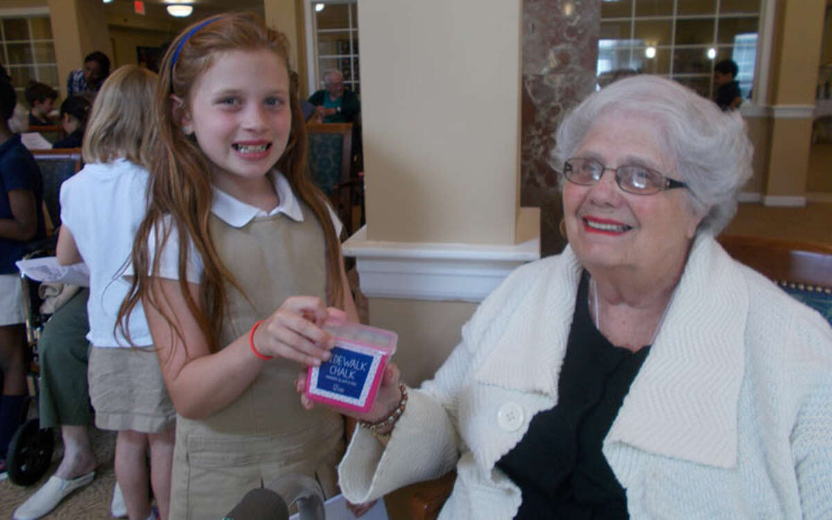 Resident Anita Schott handing the chalk to one of the first graders.