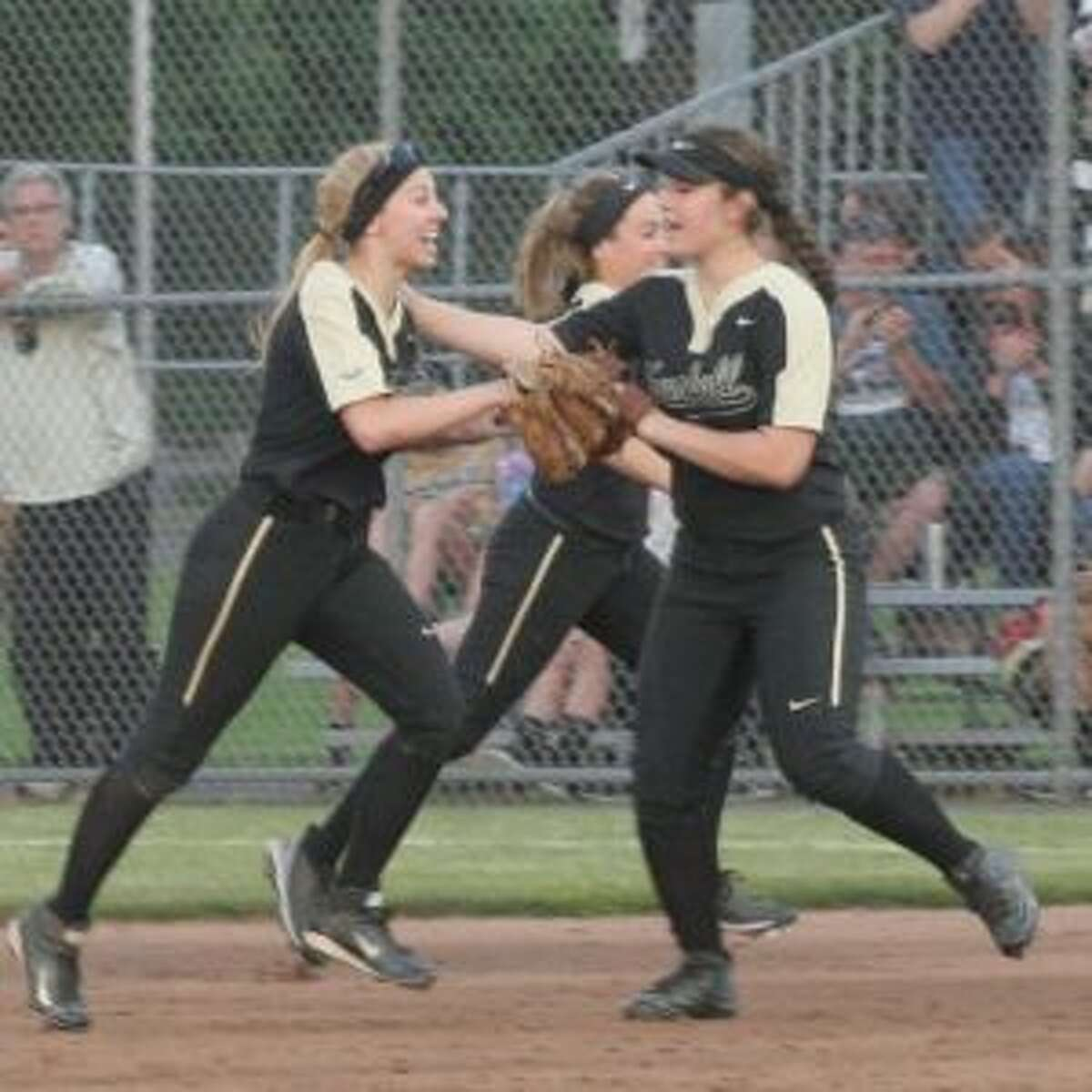 Erica Fluskey is greeted after the rightfielder's catch ended a bases-loaded, no-out jam in the fifth inning.