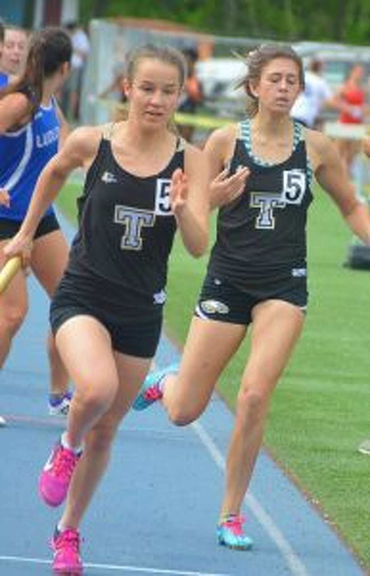 Kate Romanchick takes baton from Ashley Storino for the final leg of the 4x800 meter relay at the FCIAC championships.