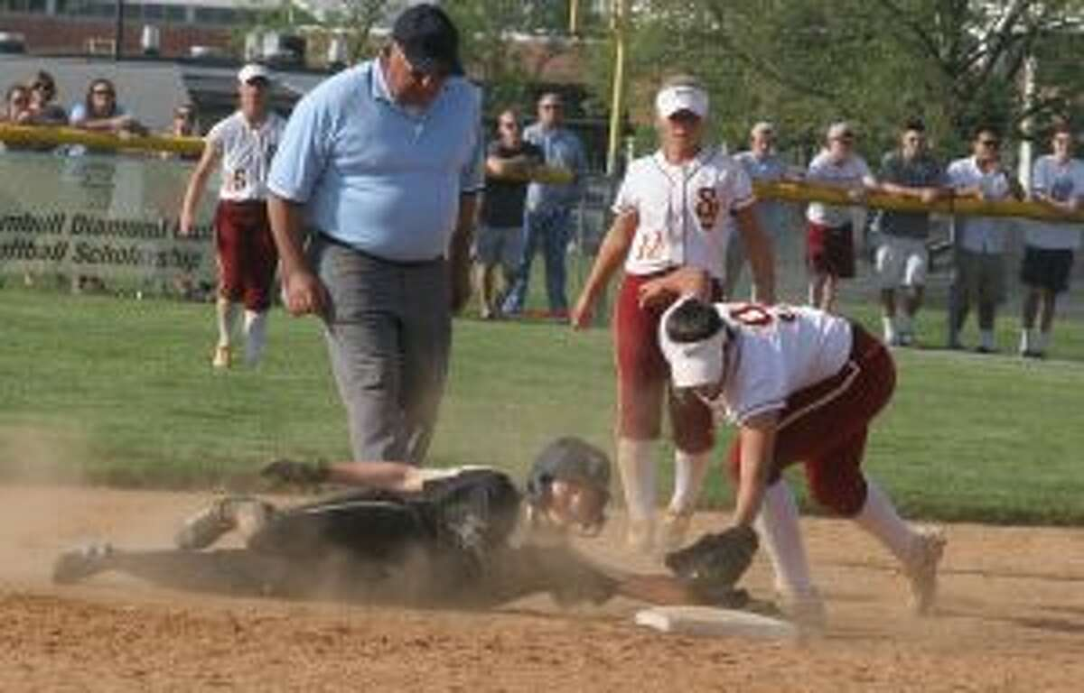 Trumbull's Maggie Coffin keeps her hand on the bag, as shortstop Kayla Giacobbe looks to get the tag down with umpire Al Vasquez in perfect position to make the safe call.
