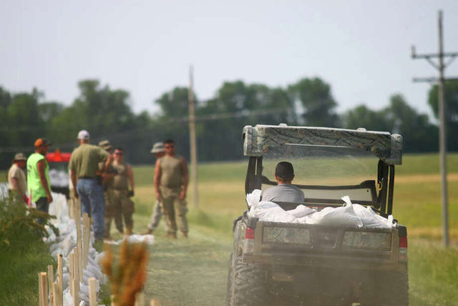 Volunteers and National Guard troops work on the levee near the Florence bridge Monday. Photo: Rosalind Essig | Journal-Courier