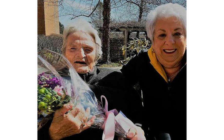 Long Hill Garden Club member Arlene DAgosto brightens the day of a St. Joseph's Manor resident.
