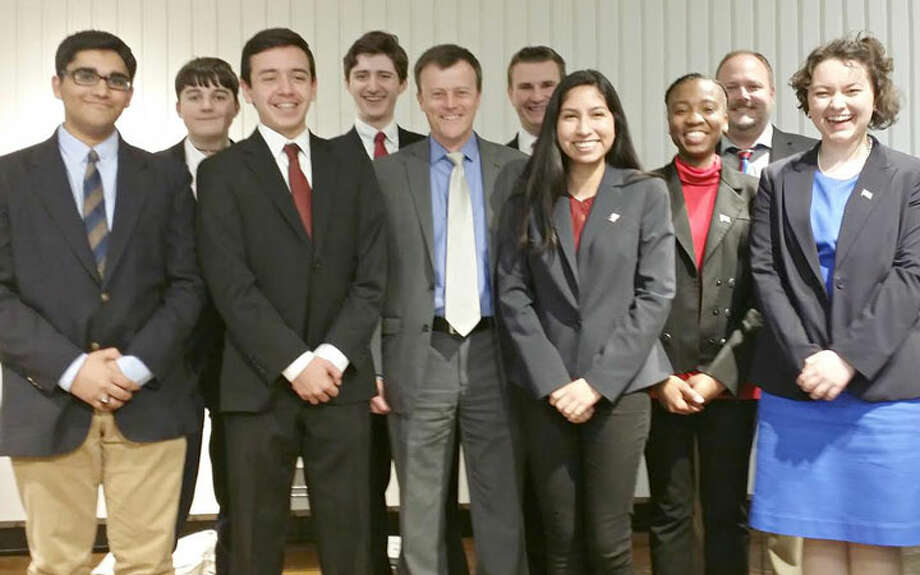 Debaters pose with Debate Moderator T. R. Rowe (fifth from left) and Trumbull Library Director Stefan Lyhne-Nielsen (second from right).