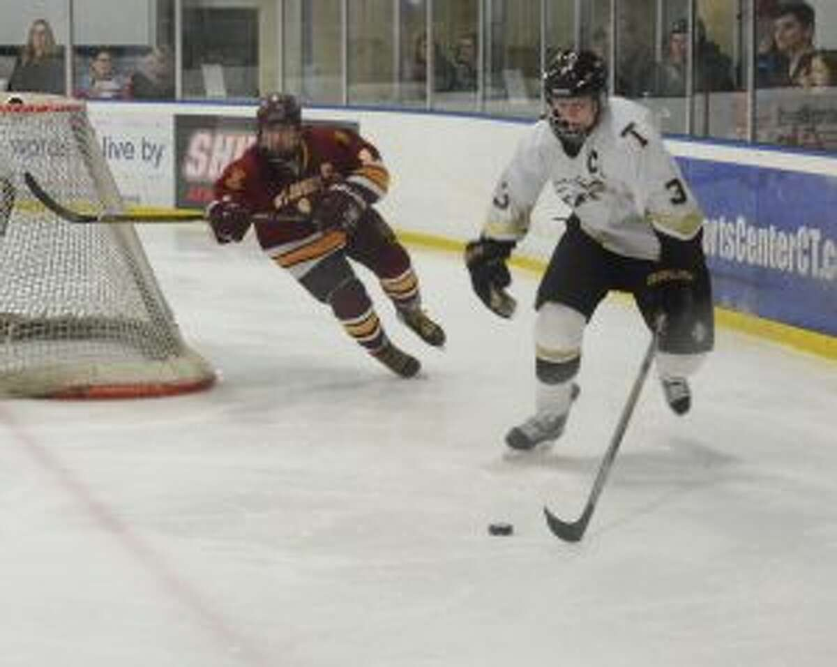 Trumbull's Jake Liebowitz works the puck around the net with St. Joseph's Will Foldesi in pursuit.