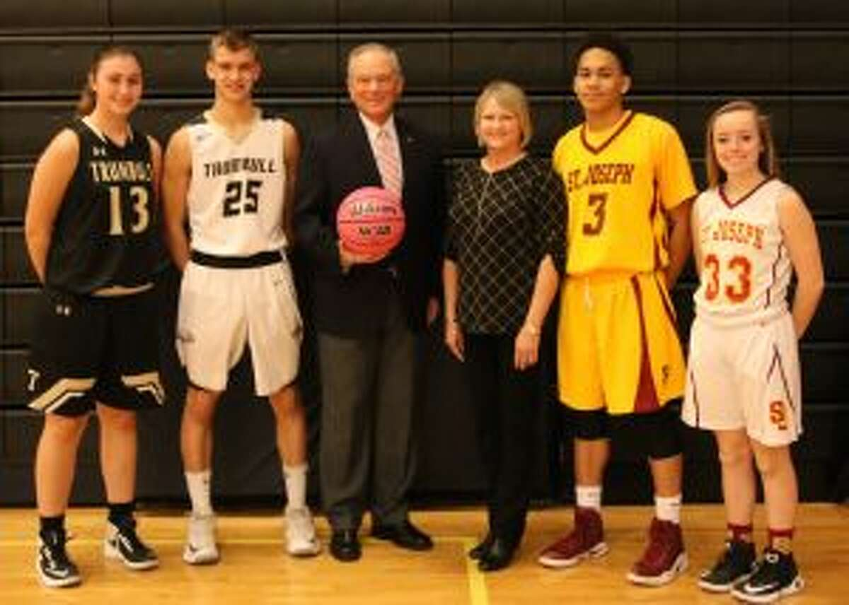 Trumbull High senior captains Claudia Tucci (13) and J.J. Pfohl (25), Joe Gintoli, International President Elect AABO, Coaches vs, Cancer Coordinator Kelly Stewart from the American Cancer Society, and St. Joseph senior captains Camren Menefee (3) and Ashley Lynch (33) gather prior to the event. - Laura Robertson photo