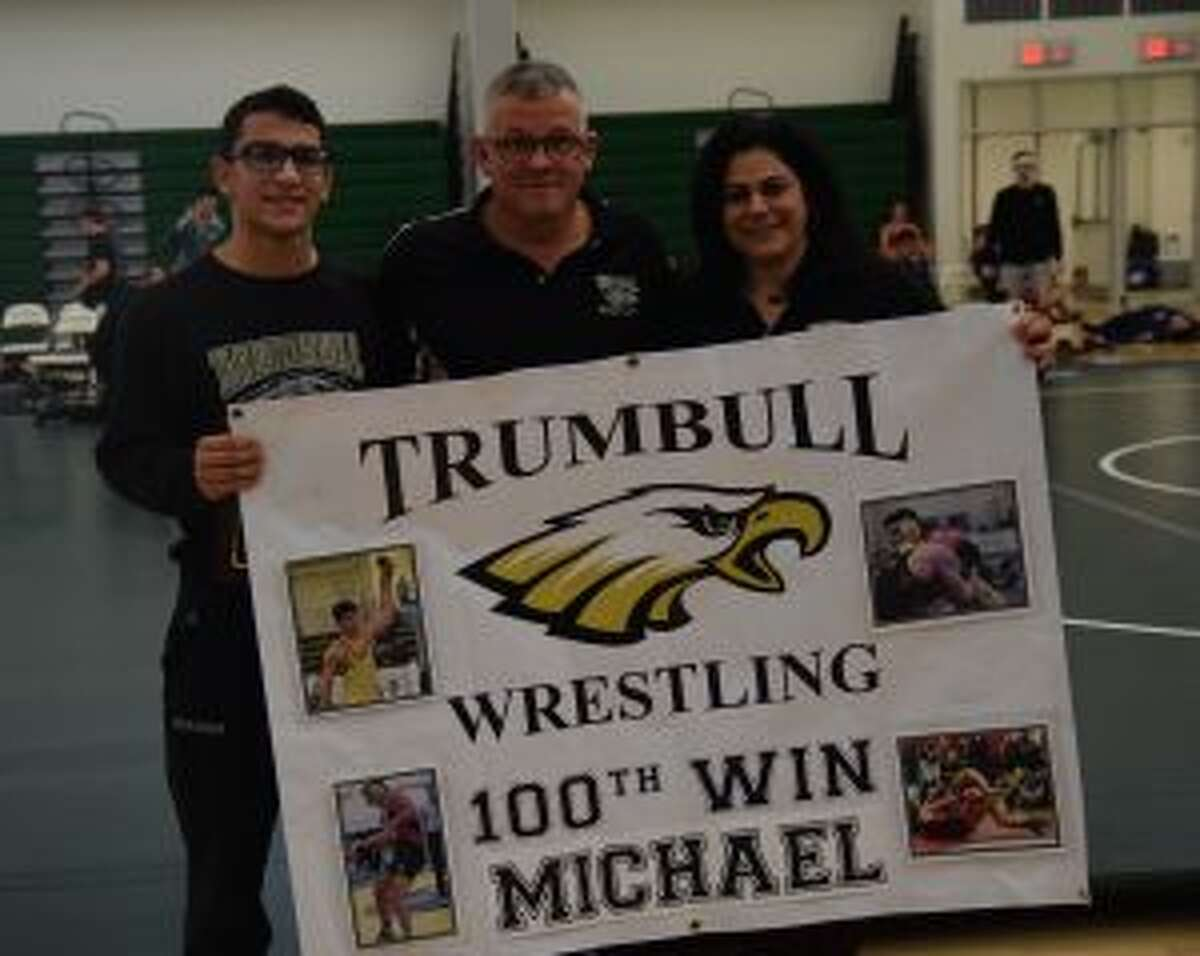Senior Michael Mirmina celebrates his 100th Trumbull High School varsity wrestling win with Coach Charlie Anderson and his mom Michele Mirmina at the Guilford Duals. - Dee Sollenberger photo