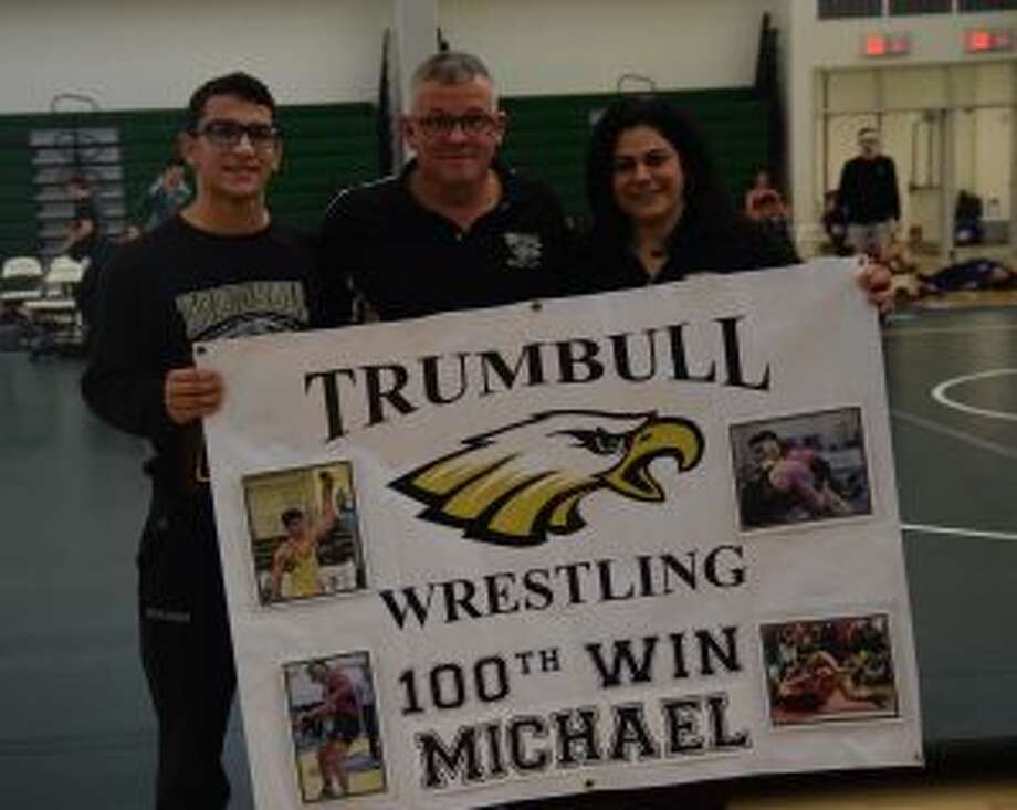 Senior Michael Mirmina celebrates his 100th Trumbull High School varsity wrestling win with Coach Charlie Anderson and his mom Michele Mirmina at the Guilford Duals. — Dee Sollenberger photo