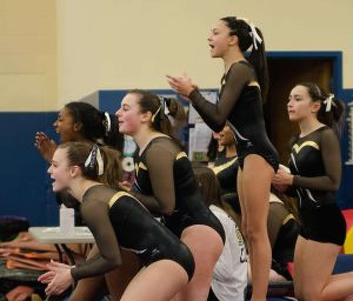 Trumbull High's Kate Burns, Chantal Boyd, Natalie Smerling, Ashleigh Johnson and Leah Karlan cheer on teammates in a tri-meet on Saturday.