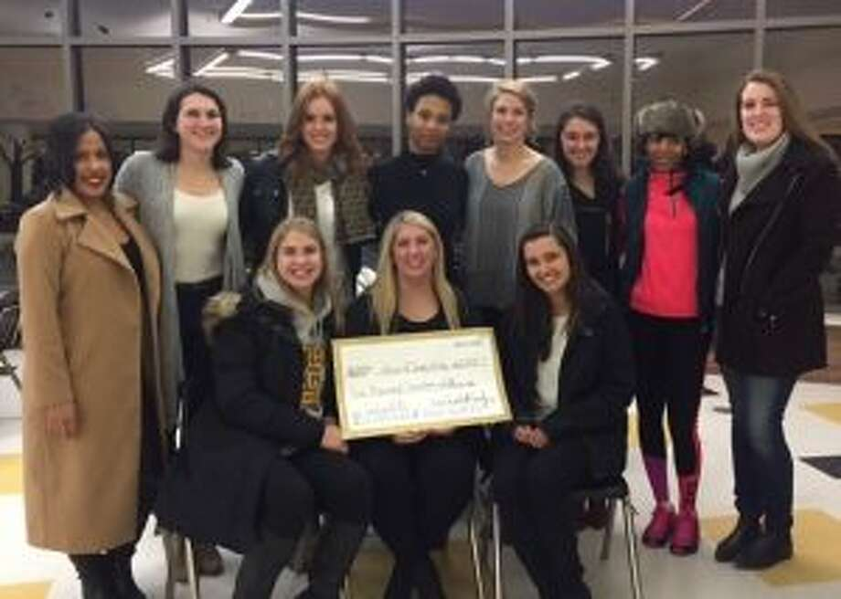 Members of the 2011 FCIAC championship team gather around teammate Allison Kirby, after she was presented with a check from Go Fund Me. Seated are Alexa Pfohl, Allison Kirby and Erin Puglia. Standing are Jackie Palmer, Kelly Coughlin, Kelly Metzger, Taisha Lima, Victoria Pfohl, Meg Puglia, Chontayvia Kennedy and Erin Moore.