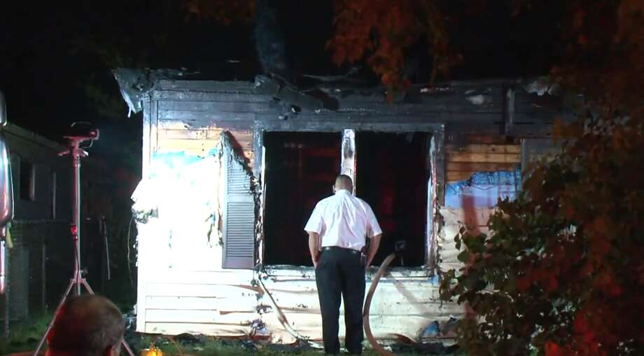 Houston firefighters late Monday clear the scene of house fire in southeast Houston, believed to be caused by a candle. A firefighter was injured while battle the blaze, authorities said. The homeowner safely got his family out. Photo: Metro Video