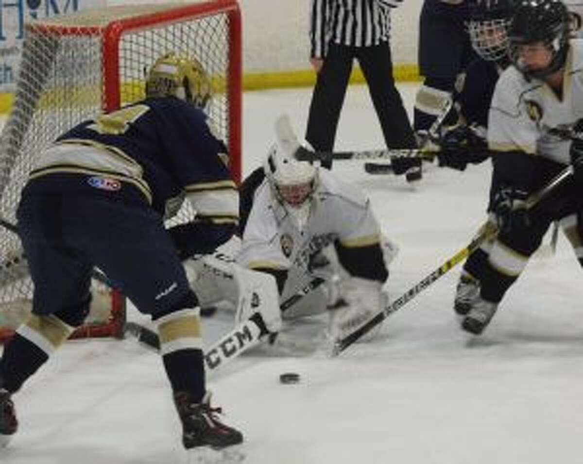 Tory Coffin goes to cover the puck with a Lancer on the doorstep.
