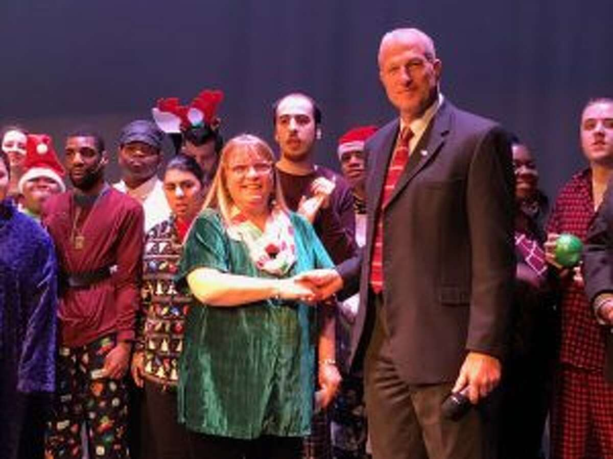 Mayor Mark Lauretti presents a donation check to Project Impact's Terry McIntosh prior to last Wednesday's production of The Polar Express at Center Stage Theatre. - Brian Gioiele photo