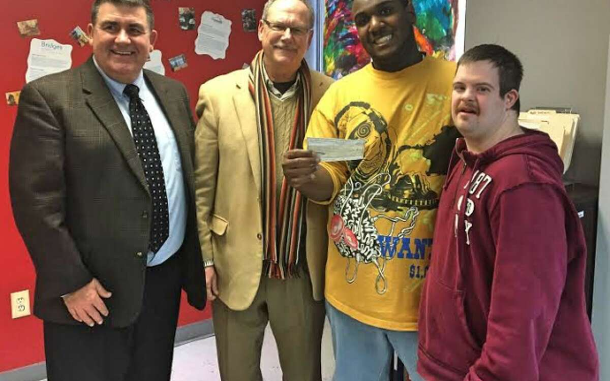 Davon Johnson and Kenny Schwab, right, accept a $20,000 donation to Project Ability from George Perham of Antinozzi Associates on behalf of Kennedy Center President & CEO Rochard Sebastian, left.